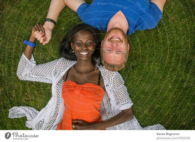 Multiracial couple in the park Lifestyle Summer Human being Young woman Youth (Young adults) Young man Woman Adults Man Couple 2 18 - 30 years Grass Red-haired