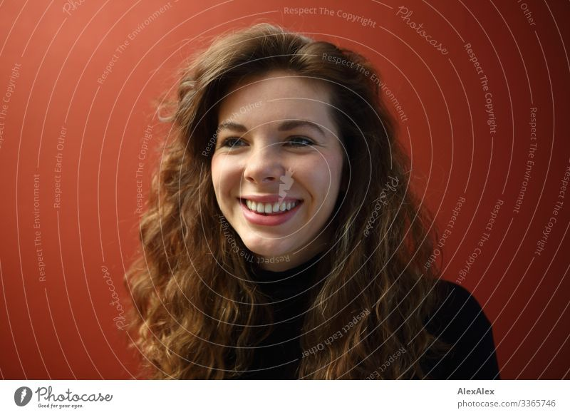 Portrait of a smiling young woman with dimples in front of a red wall Elegant Joy already Life Well-being Flat (apartment) Young woman Youth (Young adults) Face