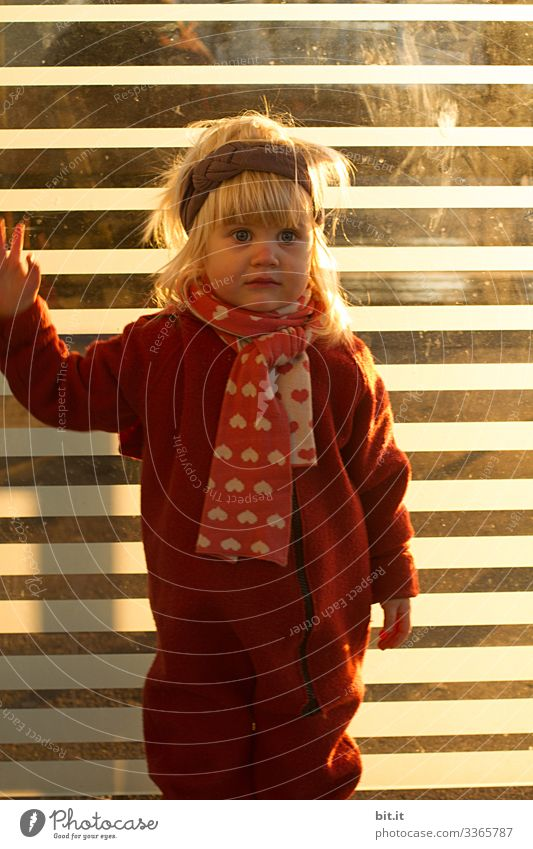 Funny, blonde girl in overalls, headband and scarf made of wool, stands at glass bus stop and waits in suspense. Cute child in warm clothes post at striped glass front, smiles lost in thought, dreamy. Cute toddler in sunlight