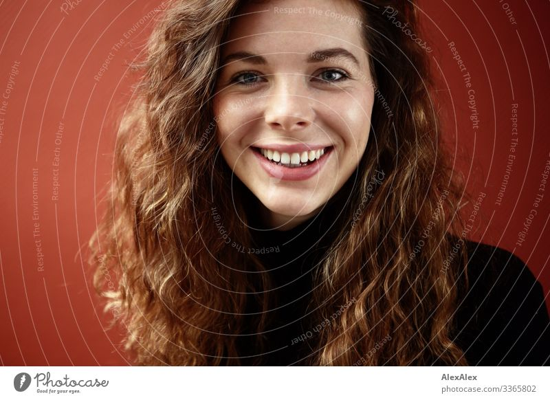 Portrait of a young woman in front of a red wall Living or residing Young woman Youth (Young adults) Face 18 - 30 years Adults Sweater Brunette Long-haired Curl