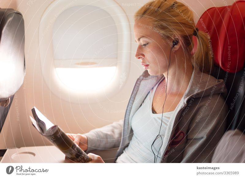Woman reading magazine and listening to music on airplane. Lifestyle Relaxation Reading Vacation & Travel Trip Entertainment Music Economy Business Human being
