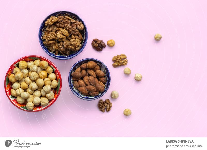 Assortment mix of nuts in bowls on pink Vegetable Nutrition Vegetarian diet Diet Plate Bowl Table Group Natural Above Pink Decline Snack Almond hazelnuts