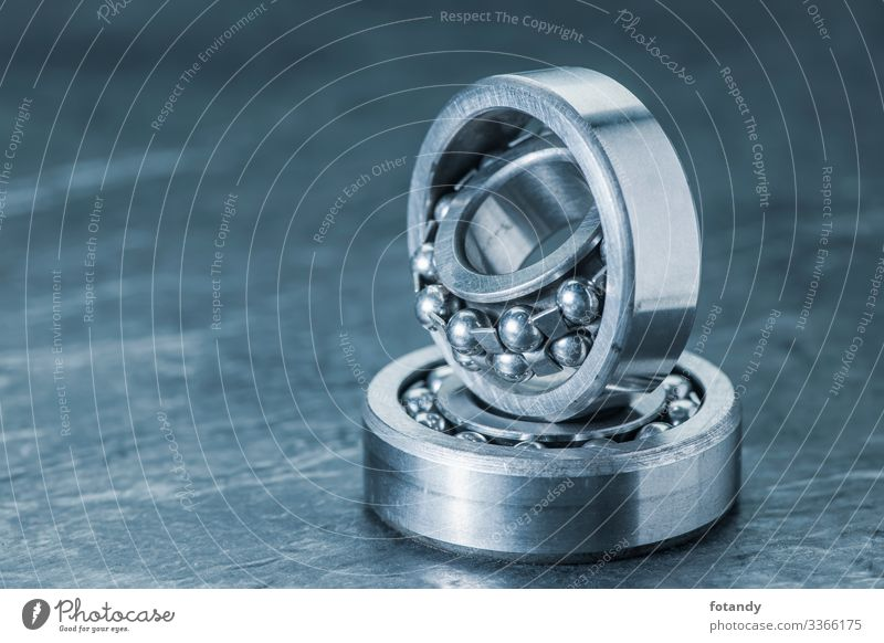 Two spherical roller bearings on slate blue toned Industry Craft (trade) Technology Metal Steel Sphere Rotate Stand Exceptional Round Blue Gray Movement