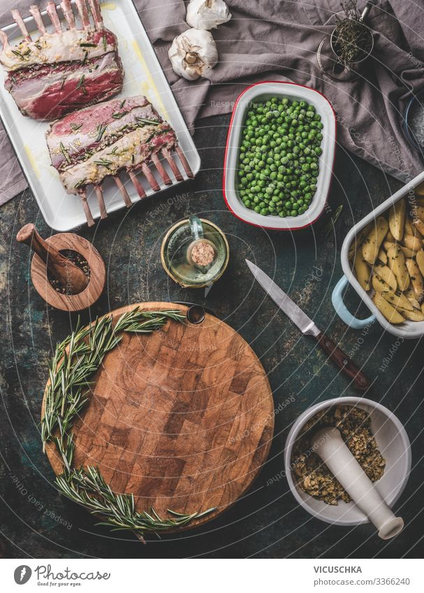 Meat food background. Cooking preparation with raw lamb meat, green green peas , back potatoes and rosemary bread crust on rustic table with empty cutting board. Top view. Racks of lamb