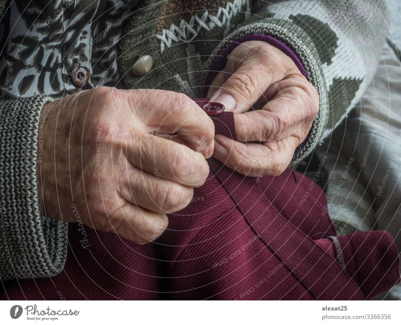 Older woman's hands sewing a button Leisure and hobbies Craft (trade) Woman Adults Grandmother Hand Age background Buttons close Embroidery grandma granny