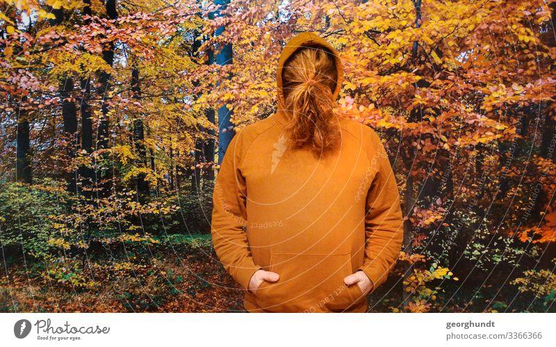Man has tied his long red hair in front of his face in a braid. He is wearing a brown-orange hooded sweater and is standing in front of a large photo of an autumn forest.