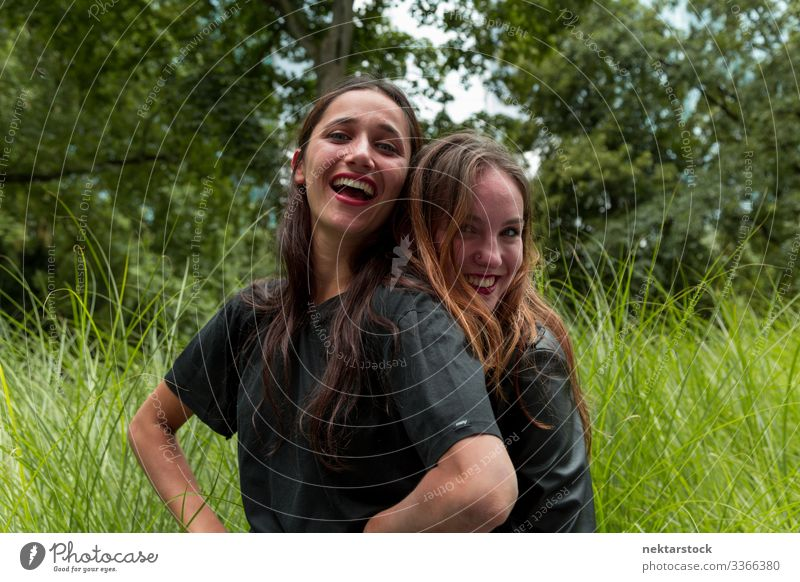 Portrait of Two Pretty Young Women Hugging and Smiling Outdoors women young adult day beauty beautiful women natural beauty females Indian ethnicity 2 people