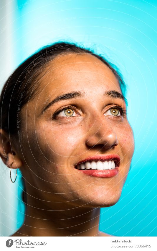 Face of Young Indian Woman Smiling on Blue Background hazel eyes female girl smile toothy smile woman young adult female beauty beautiful woman natural beauty