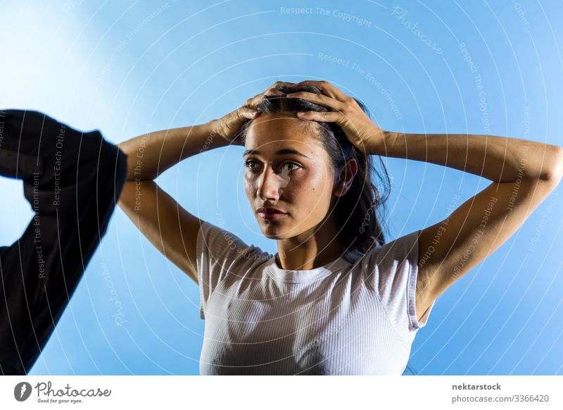 Young Woman with Hands on Head in Blue Background Studio hands on head female girl woman young adult female beauty beautiful woman natural beauty
