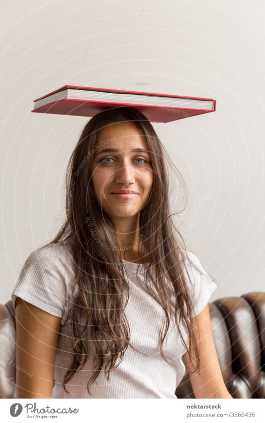 Portrait of Young Woman with Book on Head book female girl woman young adult youth culture day urban female beauty beautiful woman natural beauty