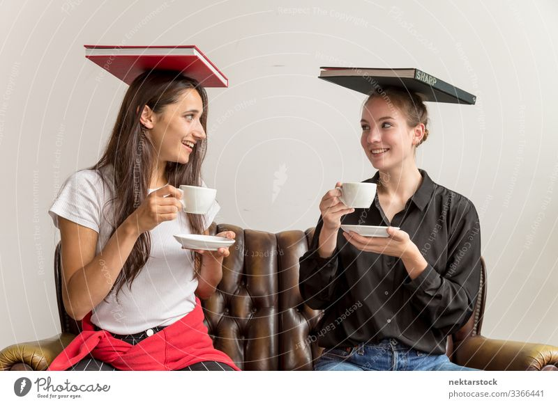 Two Young Women Balancing Books on Head and Holding Coffee Cups Making Eye Contact females eye contact looking at each other girl women young adult