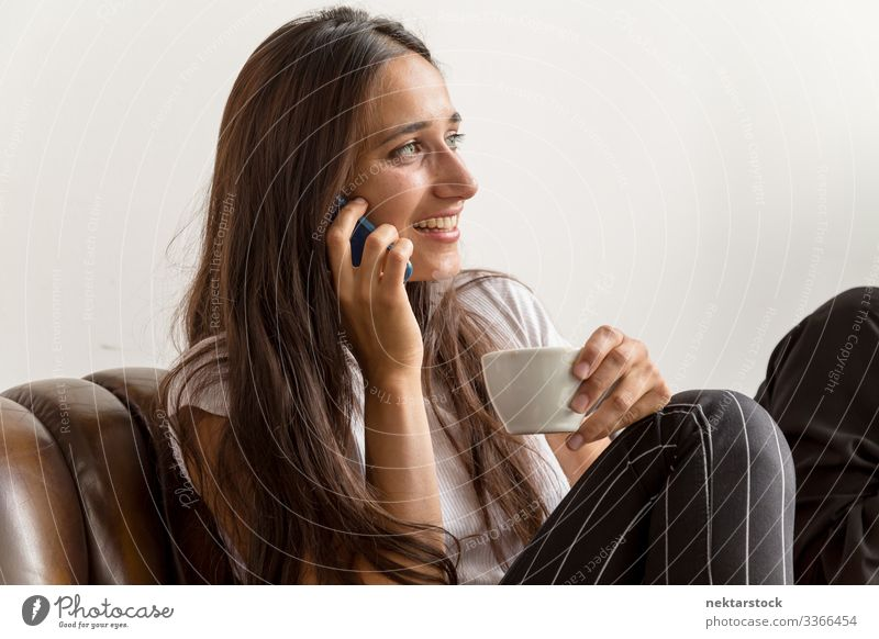 Young Woman Talking on Phone and Holding Coffee Cup phone conversation smile talking on phone female girl young adult day natural beauty real life