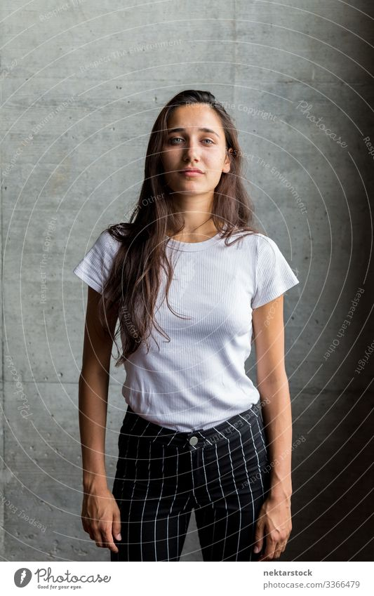 Young Woman in Front of Concrete Wall Indoors female girl woman young adult portrait serious looking at camera medium shot beautiful woman natural beauty