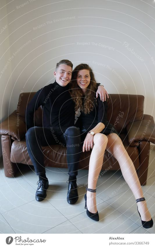 Young man and young woman sitting together on a brown leather couch and smiling Lifestyle Style Joy already Harmonious Living or residing Sofa Room Young woman