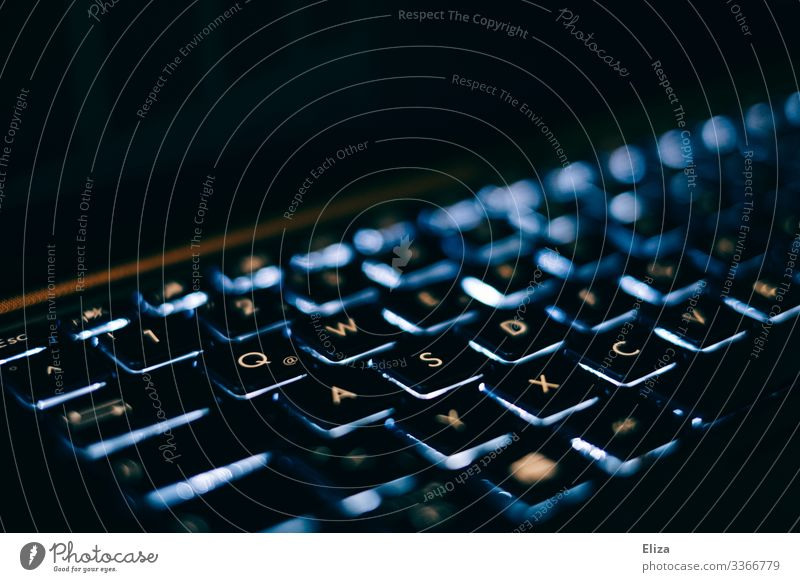 A blue glowing laptop keyboard with white letters in the dark with lots of black around it Computer Notebook Business Keyboard Illuminate Blue