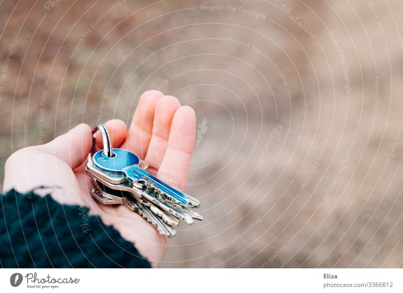 A hand that hands over a bunch of keys with a blue key on it when handing over the apartment after a move. Concept of living, living space and handing over the keys.