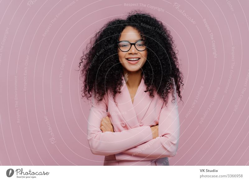 Pleased curly haired woman wears optical glasses for vision correction, elegant suit, keeps hands crossed over chest, poses against purple background, comes on job interview. Businesswoman at work