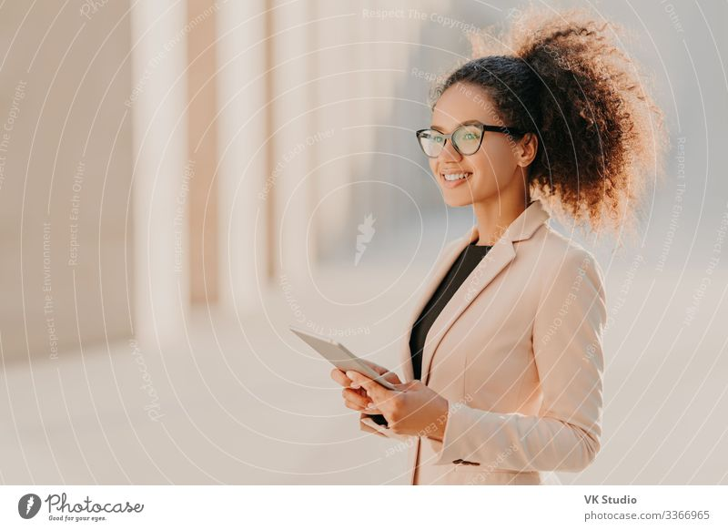 Woman with Afro hair, dressed elegantly holds tablet computer Lifestyle Elegant Style Technology Internet Human being Adults Jacket Eyeglasses Smiling Stand