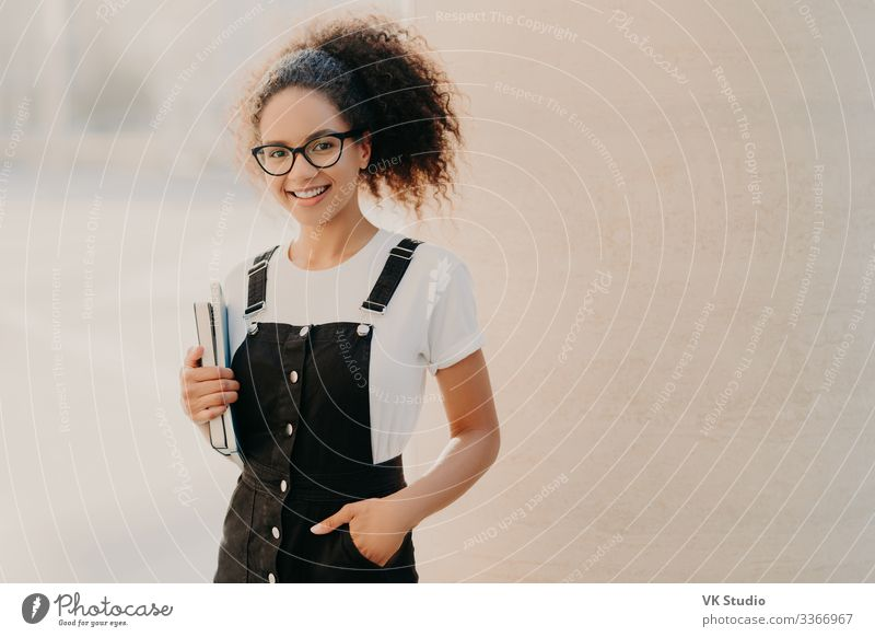 Lovely curly woman with combed hair, keeps hand in pocket Style Happy Study Academic studies Work and employment Human being Woman Adults 1 18 - 30 years