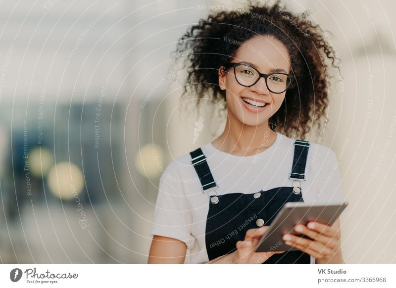 Lovely dark skinned ethnic woman holds modern touchpad Lifestyle Joy Happy Technology Internet Woman Adults Email T-shirt Shirt Eyeglasses Afro Smiling Cute
