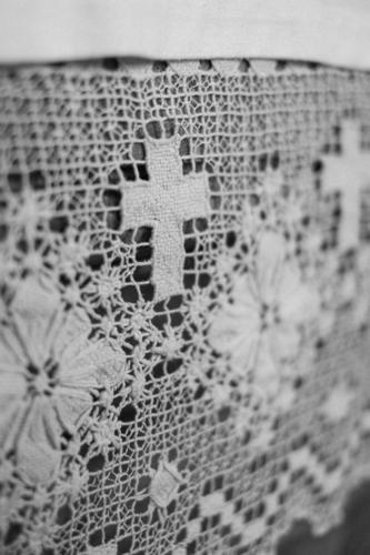 A white crocheted blanket with flowers and crucifix/cross ornaments and patterns in the church Crocheted decorative blanket doily Pattern Ornament Church