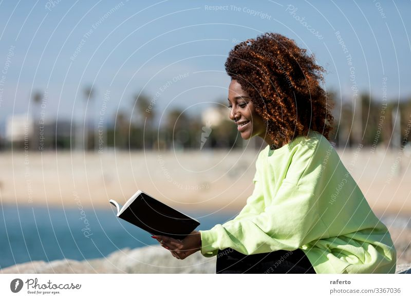 Side view of a afro woman sitting on shore reading a book Lifestyle Style Beautiful Reading Ocean Human being Feminine Young woman Youth (Young adults) Woman