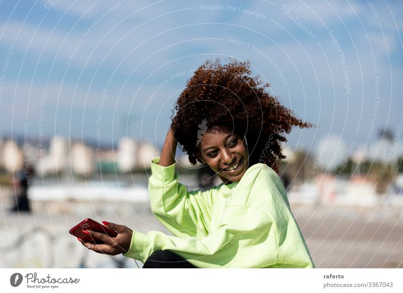 Beautiful afro woman sitting on shore using a mobile phone Style Happy Beach Telephone PDA Human being Feminine Young woman Youth (Young adults) Woman Adults 1