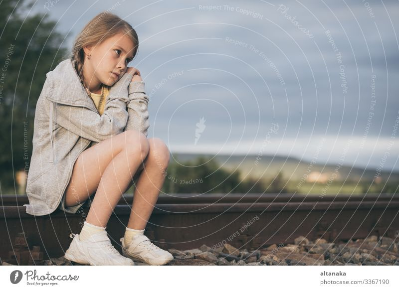 Portrait of young sad girl sitting outdoors on the railway at the day time. Concept of sorrow. Face Child Human being Woman Adults Family & Relations Infancy