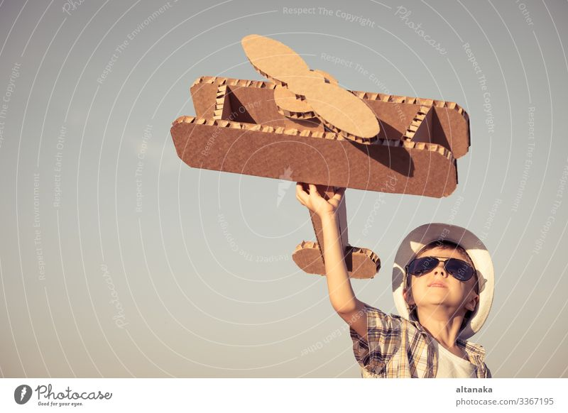 Little boy playing with cardboard toy airplane in the park Lifestyle Joy Happy Playing Vacation & Travel Adventure Freedom Summer Sun Sports Success Child Pilot