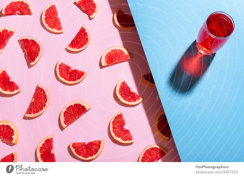 Grapefruit drink on blue background. Fresh grapefruit slices Beverage Cold drink Lemonade bicolor Blue background Citrus fruits colorful detox beverage duotone