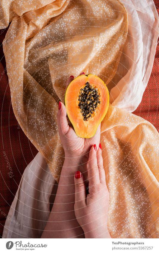 Papaya half hold in woman hands on tablecloths. Fruit Dessert Breakfast Organic produce Vegetarian diet Diet Exotic Healthy Eating Sweet Orange above view