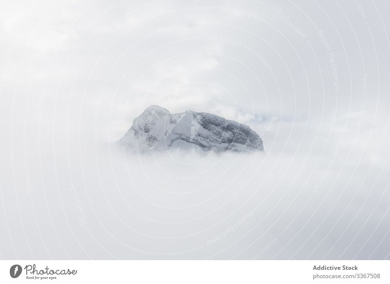 Snow peak surrounded by cloudy sky in fog mountain nature scenery rocky scenic hiking snow winter snowy travel hill natural bright weather conditions high