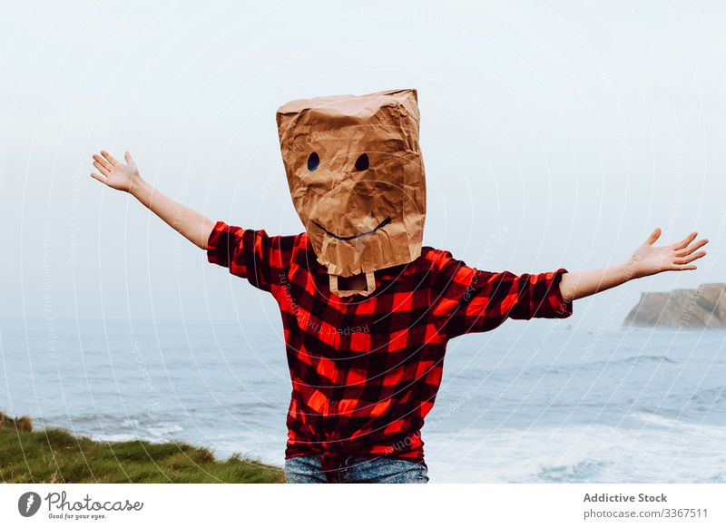 Person with paper bag on head jumping on shore plastic package ecology concept environment person gesture sign nature pollution problem packet polyethylene