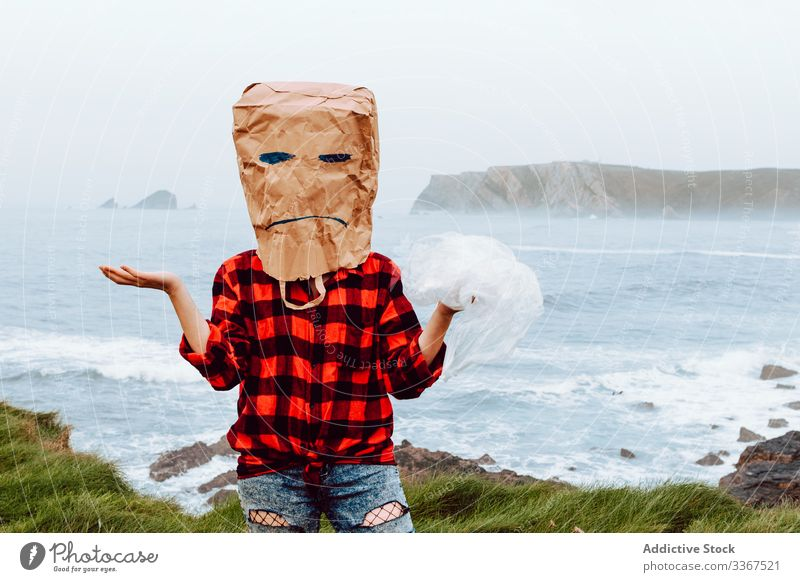 Person with paper bag on head holding plastic package ecology concept disapproval dislike disagree environment person gesture sign nature pollution problem