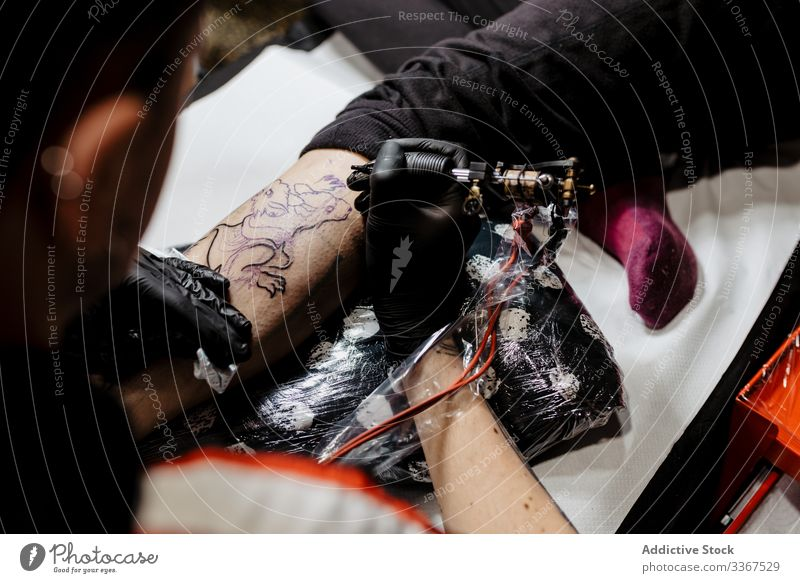 Anonymous crop tattooist working with client in salon man tool stylish subculture artist master creative fashion professional tattooer modern contemporary