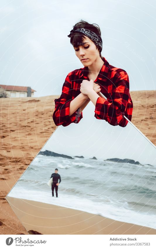 Sad woman with big mirror standing on beach concept reflection sea serious sad surfer couple pensive stormy casual young female ocean sand water thoughtful
