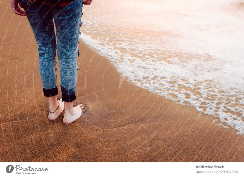 Woman dressed in jeans standing on beach woman barefoot barefooted hipster sea sand stormy wear female style personality ocean water nature travel coast seaside
