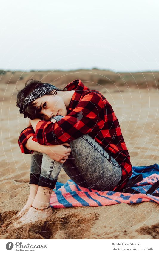 Thoughtful hipster woman sitting on sandy beach pensive serious young relax thoughtful sea casual female ocean observation think red nature travel coast seaside