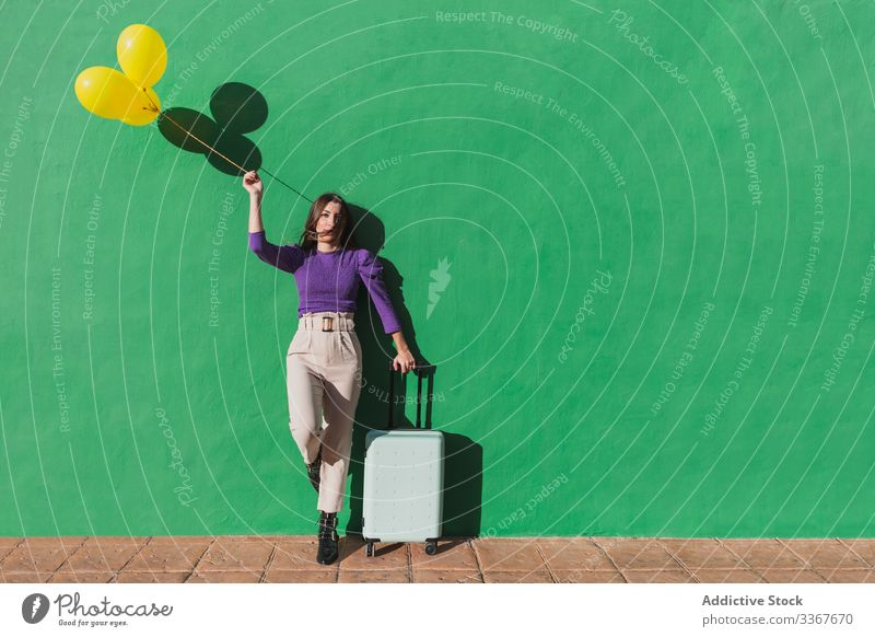 Young woman with balloons and suitcase standing next to green wall travel holiday vacation happy carefree young luggage tourism journey female bag stylish