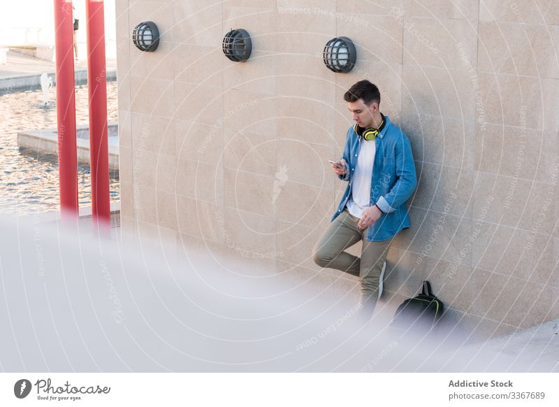 Student in headphones browsing smartphone leaning on wall student backpack using education man gadget campus building college surfing youth recreation device