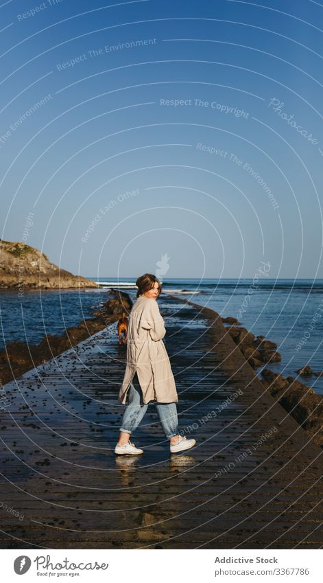 Woman with dog walking along wet pier against calm sea water and rocky coast in sunny day woman companion fresh pet ocean spain tranquil mastiff owner beach