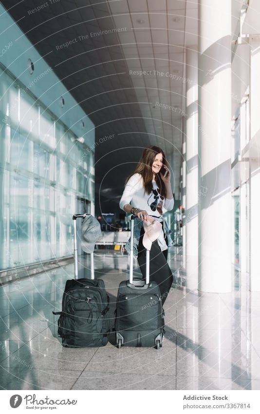 Calm woman using phone in airport talking surfing baggage vacation departure arrival adventure female wait smartphone delay public destination browsing explore