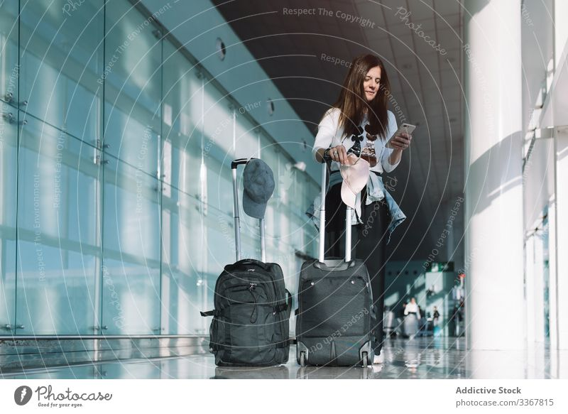 Calm woman using phone in airport surfing baggage vacation departure arrival adventure female wait smartphone delay public destination browsing explore holiday