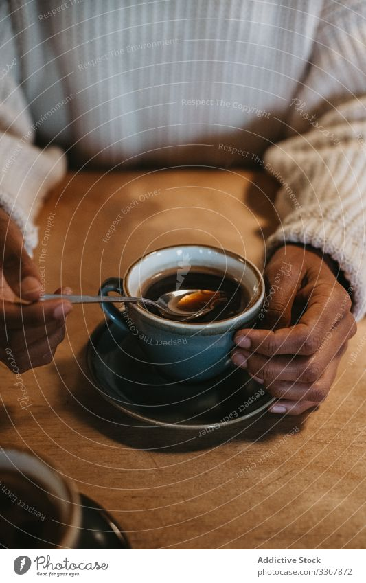Anonymous woman with coffee cup in cafe hand adult female person sitting enjoying fresh hot brewed mug drink beverage black table wooden cafeteria indoors