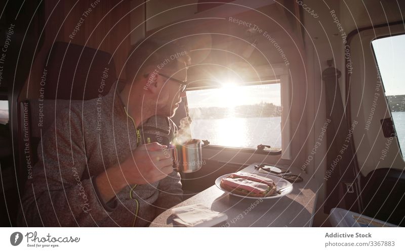 Focused male hiker having breakfast in van in Ireland man sunrise vehicle morning watch motorhome window mobility tourist trailer vacation journey car tourism