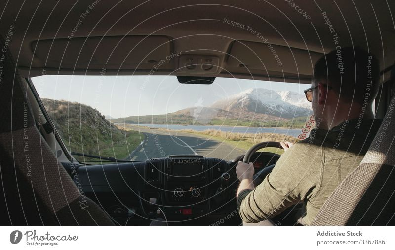 Unrecognizable man driving car in Ireland drive road ride vehicle mountain terrain holiday male auto steer transportation travel speed trip tourism fast