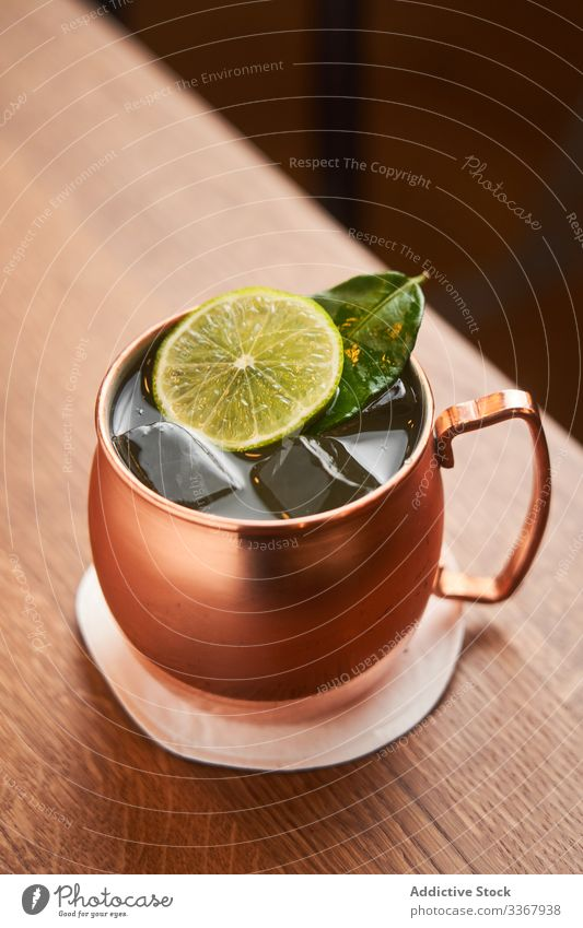 Moscow Mule cocktail in copper mug alcohol classic moscow mule vodka whiskey drink beverage lime beer ginger bar yellow counter cold luxury aperitif traditional