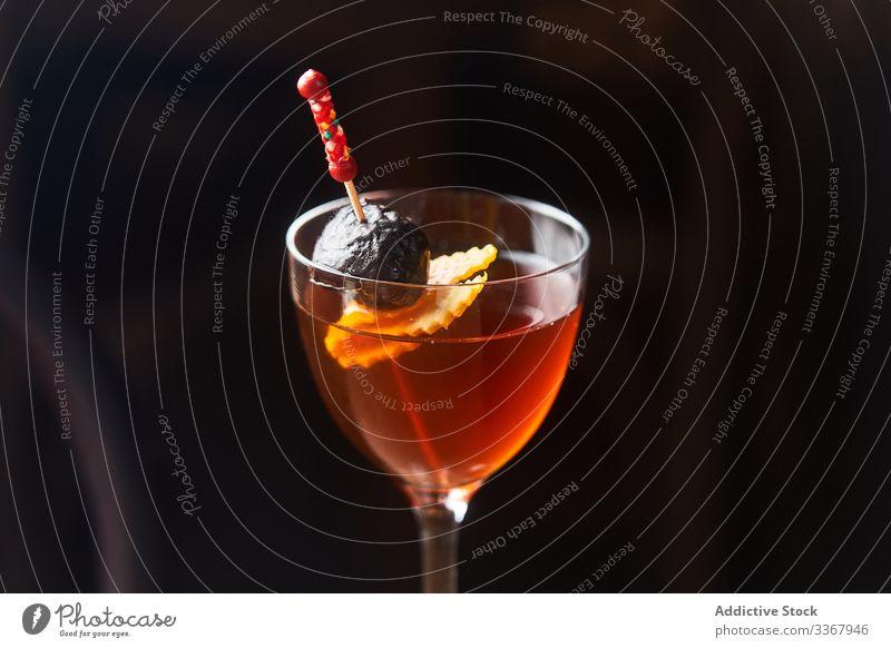 Manhattan cocktail with garnish on dark background alcohol classic manhattan drink red bourbon vermut glass bar cold luxury aperitif food fresh orange liquid