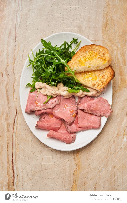 Tasty meat with bread and arugula dish plate ham jamon restaurant fresh green herb table wooden salad slice stylish elegant haute cuisine luxury rich savory