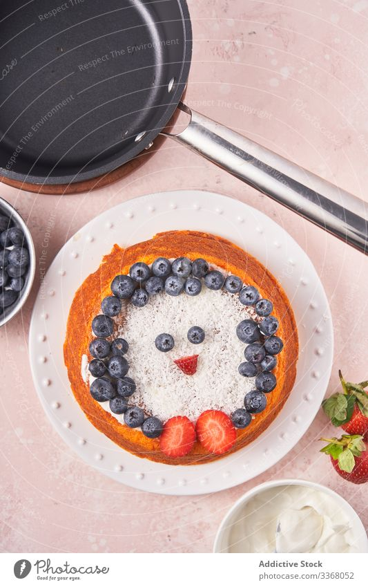 Cake with berries on plate cake baked dessert cooking decorating blueberry strawberry sour cream female chef homemade household penguin dish bowl coconut hand